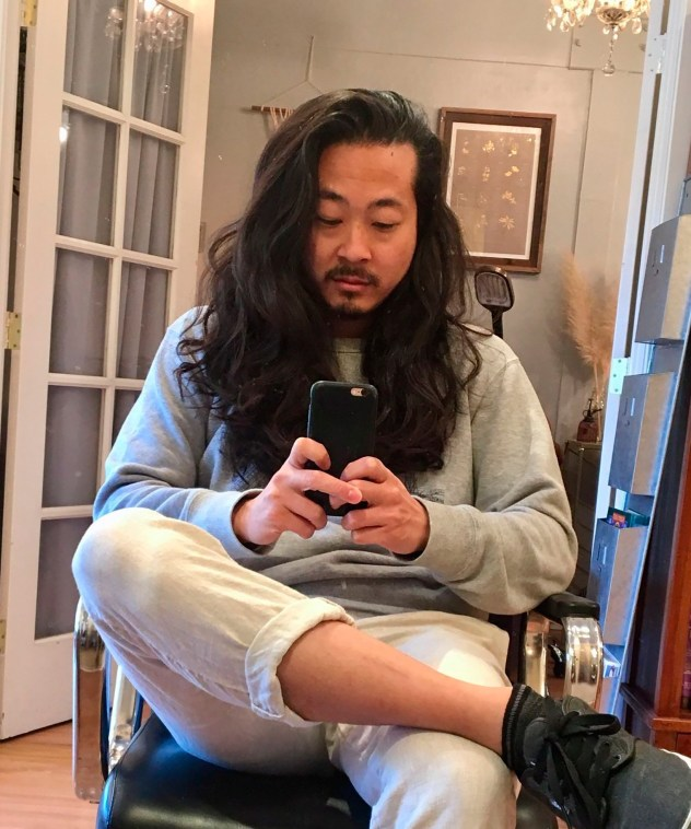 Tyler Lau pictured sat on a chair using his mobile phone in his social media work