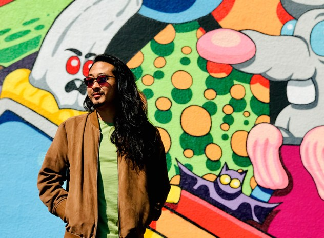 Tyler Lau stood in front of a colorful mural